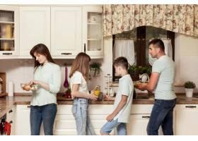 父母和孩子在厨房里为晚餐准备食物_9266480