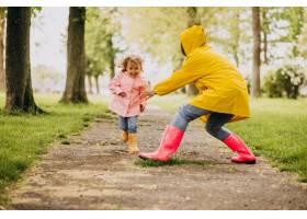 母亲和女儿在雨天在公园里玩耍_8828052
