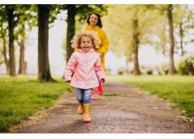 母亲和女儿在雨天在公园里玩耍_8828053