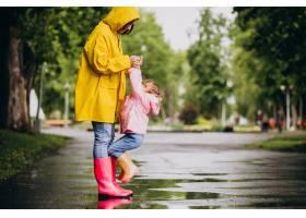 母亲和女儿在雨天在公园里玩耍_8828063