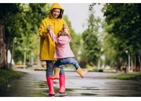 母亲和女儿在雨天在公园里玩耍_8828064