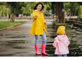 母亲和女儿在雨天在公园里玩耍_8828077
