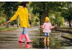 母亲和女儿在雨天在公园里玩耍_8828078