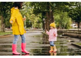 母亲和女儿在雨天在公园里玩耍_8828079