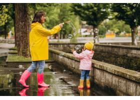 母亲和女儿在雨天在公园里玩耍_8828080