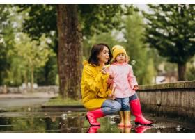 母亲和女儿在雨天在公园里玩耍_8828081