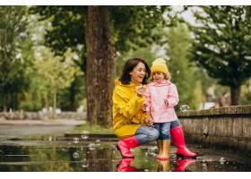 母亲和女儿在雨天在公园里玩耍_8828082