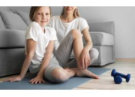 母亲和女孩在垫子上举重训练_8623074