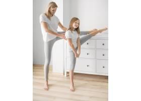 母亲和女孩在家里伸展身体_8623056
