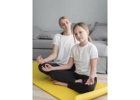 母亲和女孩在家里练习瑜伽_8623057