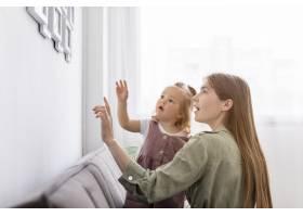母亲和女孩看着相框_8445693