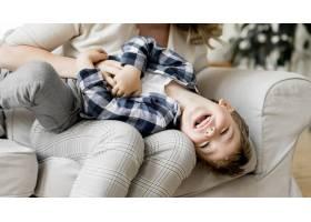 母亲和孩子一起在沙发上玩耍_8684099