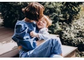 母亲带着她的儿子坐在楼梯上_8380074