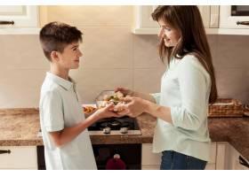 母亲带着儿子在厨房做饭_9266470
