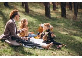 母亲带着孩子在森林里野餐_7869903