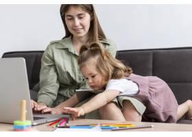 母亲带着孩子在笔记本电脑上工作_8445706