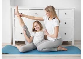 母亲帮助女孩伸展身体_8608086