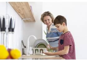 母亲看着儿子洗手的侧观_7747657