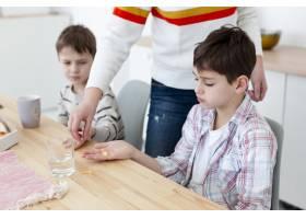 母亲给孩子服用维生素以保护他们免受病毒侵_7747649