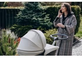 年轻的母亲推着婴儿车在公园里散步打电话_7869451