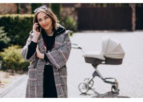 年轻的母亲推着婴儿车在公园里散步打电话_7869742