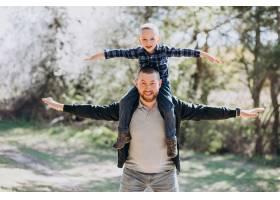 年轻的父亲带着年幼的儿子在树林里_7870165