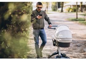 年轻的父亲推着婴儿车在公园里散步_7869414
