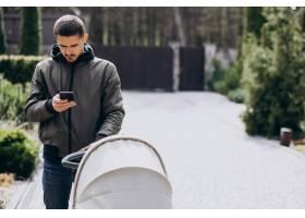 年轻的父亲推着婴儿车在公园里散步_7869981