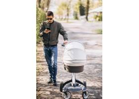 年轻的父亲推着婴儿车在公园里散步_7870157