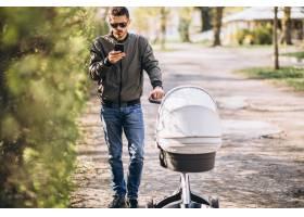 年轻的父亲推着婴儿车在公园里散步_7870166