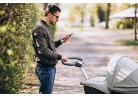 年轻的父亲推着婴儿车在公园里散步_7870176