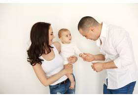 幸福美丽的年轻家庭带着婴儿微笑拥抱着_9028814