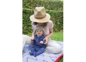 小女婴坐在格子花呢上年轻的妈妈戴着帽子_9172167