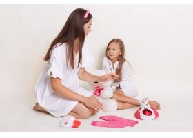 小女孩和怀孕的母亲坐在地板上周围都是童_9239126