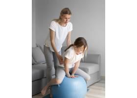 妈妈和女孩带着球锻炼身体_8623136
