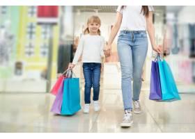 孩子和母亲商店里有五颜六色的购物袋_8792603