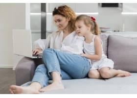 女人和女儿坐在沙发上_8009777