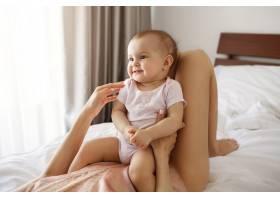可爱可爱的小女儿坐在她年轻的妈妈身上_9028530