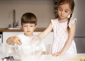 可爱的兄弟姐妹在家里做饭的前景_9007135