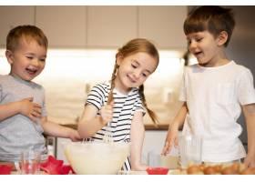 可爱的兄弟姐妹在家里做饭的前景_9007139