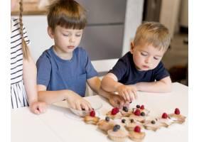 可爱的兄弟姐妹在家里做饭的前景_9007140