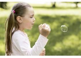 可爱的女孩用她的玩具吹泡泡_9009968