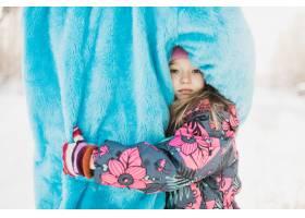 可爱的小女孩拥抱着一个穿着蓬松的蓝色服装_9184830