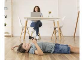 儿子在妈妈旁边玩智能手机_7728149