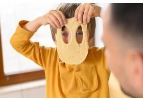 儿子戴着滑稽的面团面具_7773176