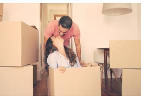 兴高采烈的年轻男子拖着盒子带着他的女朋_13145761