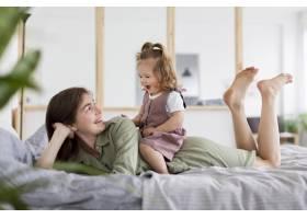 全景拍摄的母亲和女孩在床上_8445677