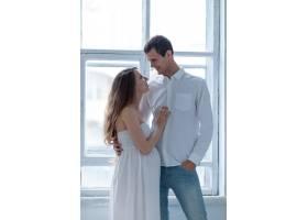 兴高采烈的年轻夫妇穿着白衣坐在沙发上_8049711