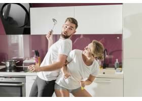一对情侣在厨房前景的室内跳舞_9010381