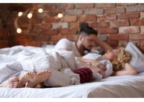 一对穿着内衣躺在床上说话的夫妇_9108416